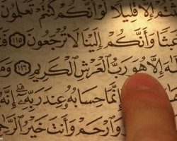 finger_pointing_to_a_verse_in_quran_book-other
